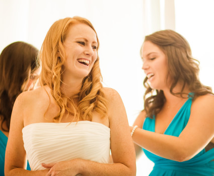 Putting on dress with help of bridesmaids